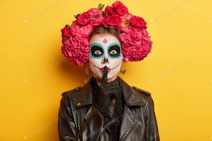 Mysterious mexican woman wears sugar creative makeup and makes silence gesture prepares for day of d