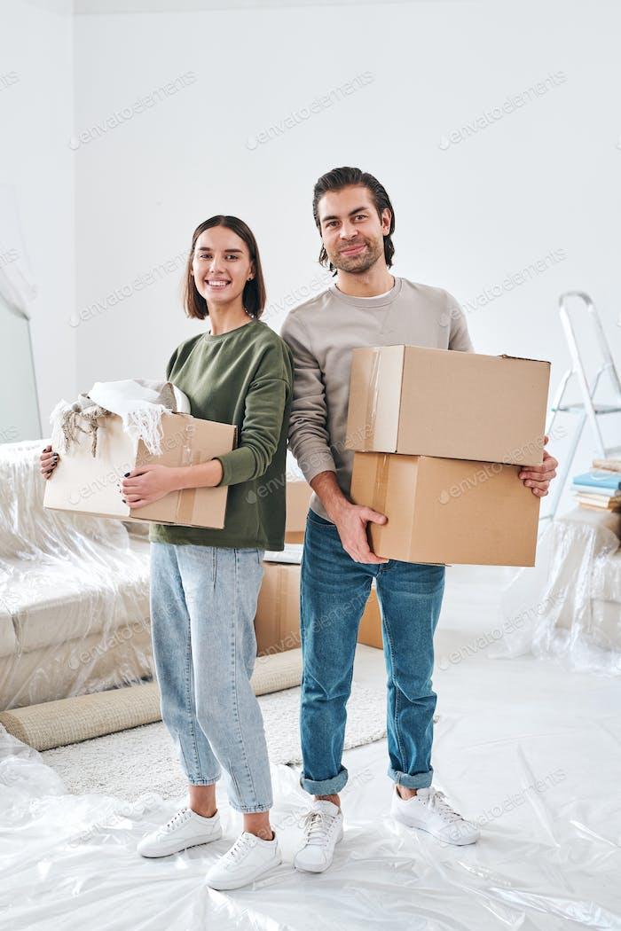 Fröhliches junges Paar in Freizeitkleidung halten Kartonboxen mit verpackten Sachen