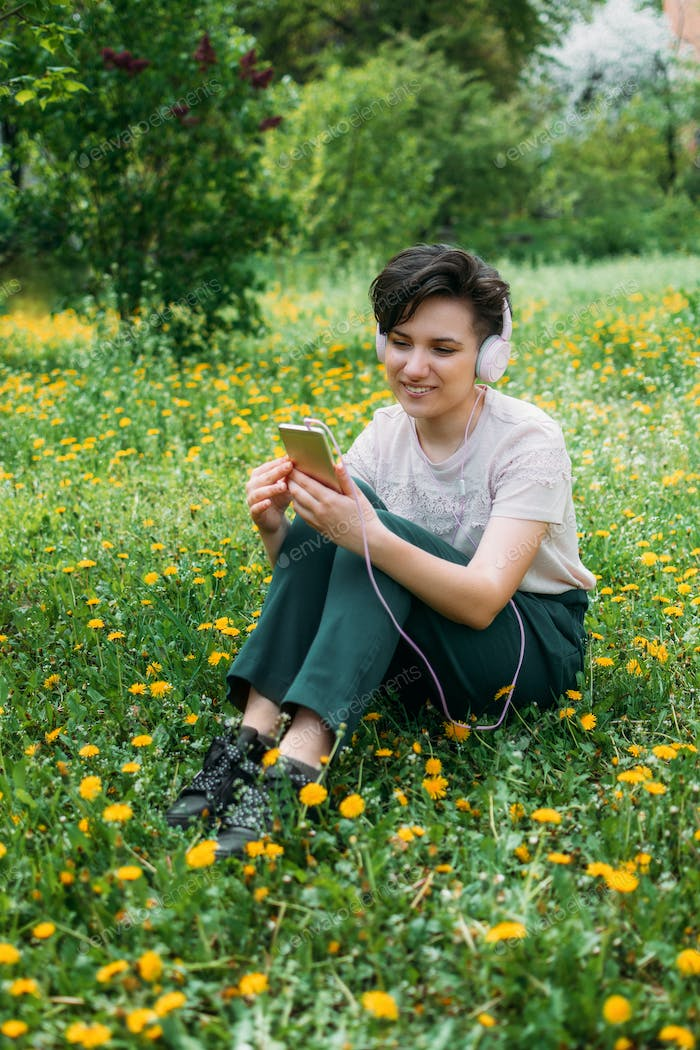 Young woman in headphones and with smartphone using audio chat social networking app, listening