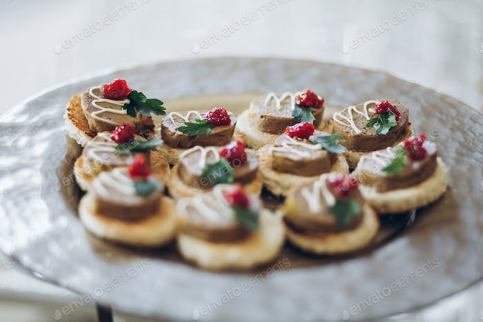 Delicious canape with paste on plate on table