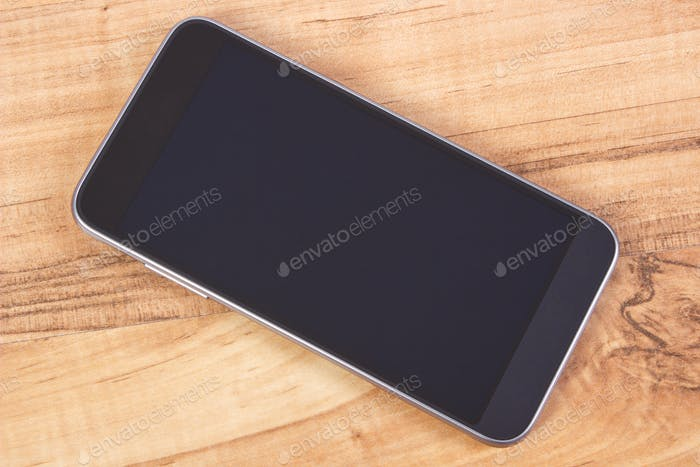 Mobile phone with blank screen on table, using smartphone concept