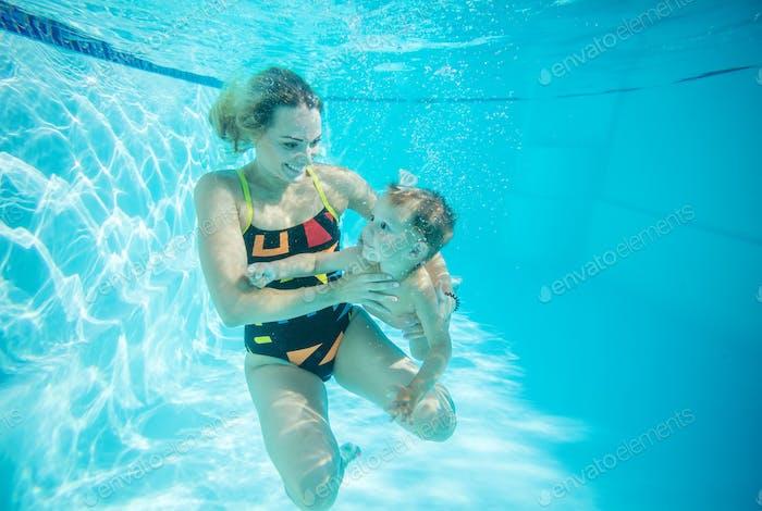 Junge Frau und kleiner Sohn schwimmen unter Wasser