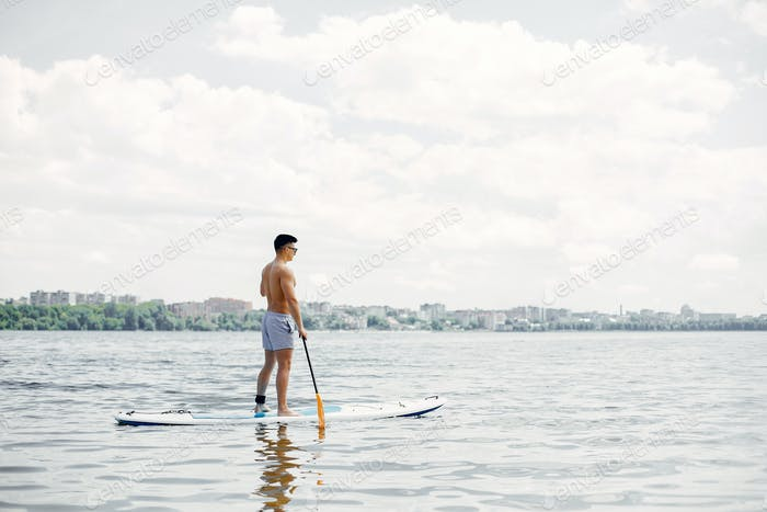 Sup surfer on a summer beach
