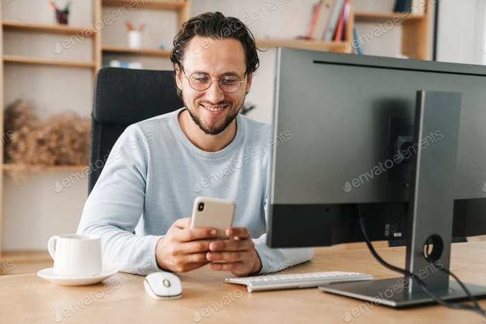 Image of programmer man using cellphone while working with computer