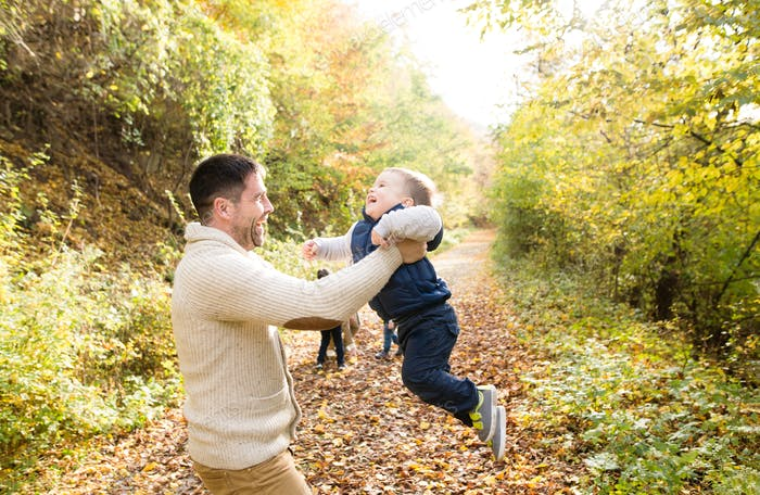 Father holding his little son, spinning him. Autumn nature.