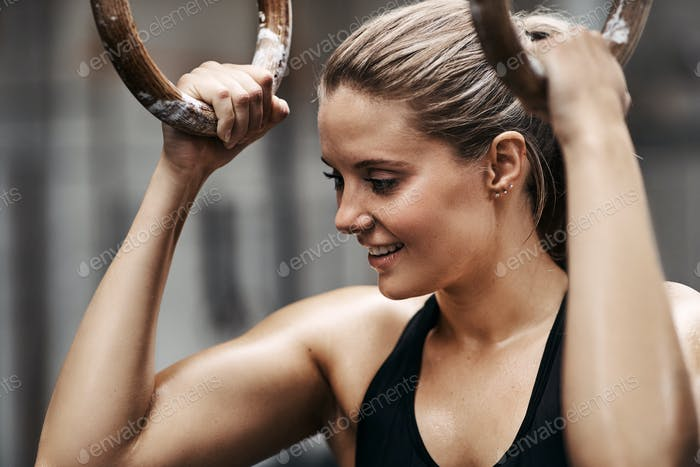 Fit woman smiling and exercising on rings in a gym