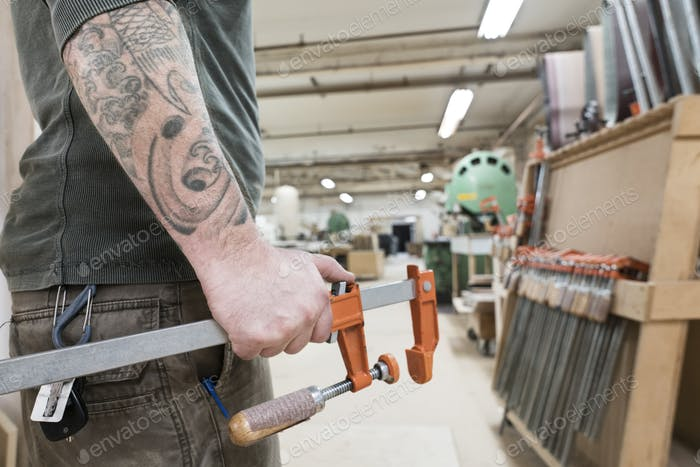 Closeup of an arm with tatoos and a hand holding a bar clamp in a large woodworking factory.