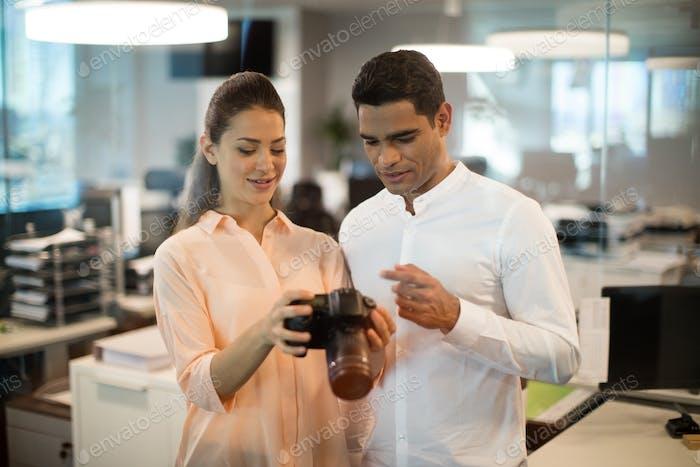 Geschäftsfrau zeigt Kamera an Kollegen im Büro