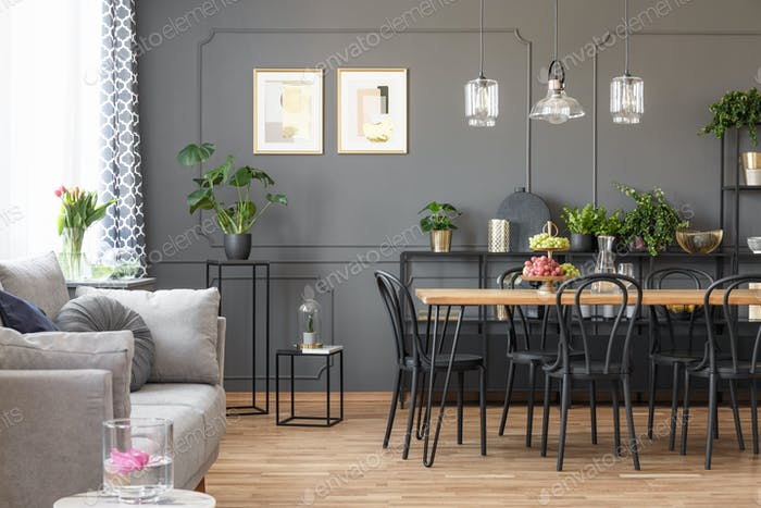 Grey sofa near black chairs at table under lamps in open space i