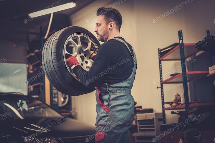 Mecánico de coche profesional de equilibrio de la rueda del coche en el equilibrador en au
