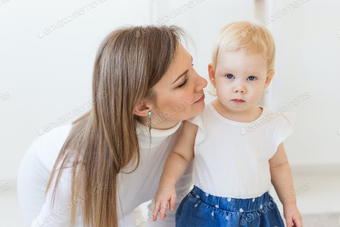 Young mother playing with her baby girl at home. Motherhood, infant and children concept