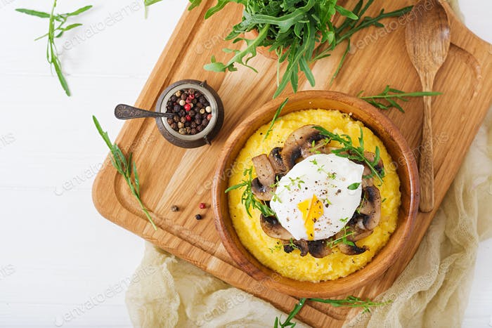 Breakfast. Polenta with mushrooms and poached egg. Flat lay. Top view.