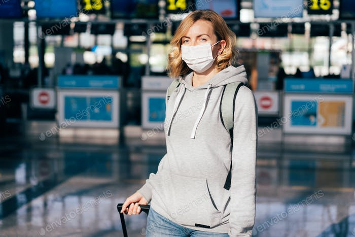 Woman passenger in a medical mask at the airport.