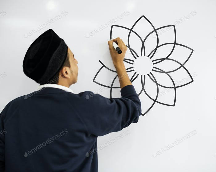 Young Muslim man writing on a whiteboard