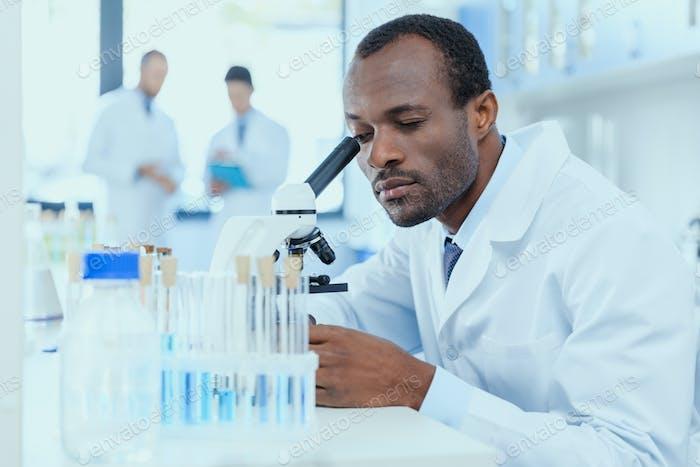 Afroamerikanischer Wissenschaftler im weißen Mantel arbeiten mit Mikroskop im Labor, Labor