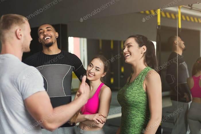 Group of sporty people talking at gym