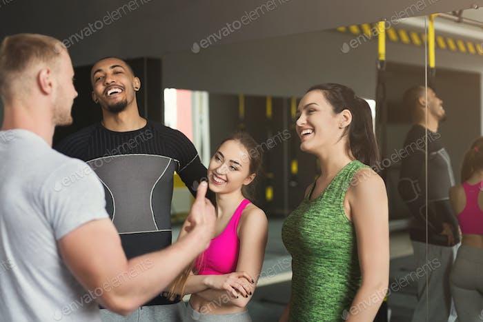 Gruppe von sportlichen Menschen, die im Fitnessstudio sprechen