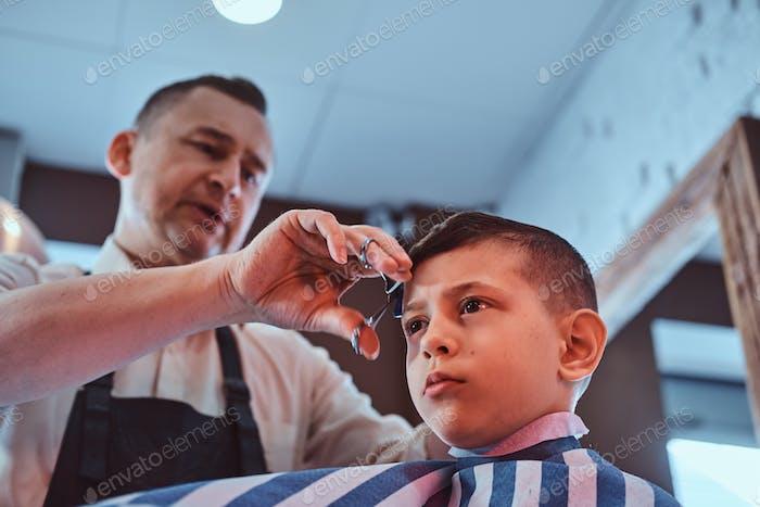 Kleine Schuljunge wird immer trendy Haarschnitt von abgelaufenen Friseur im modernen Friseur