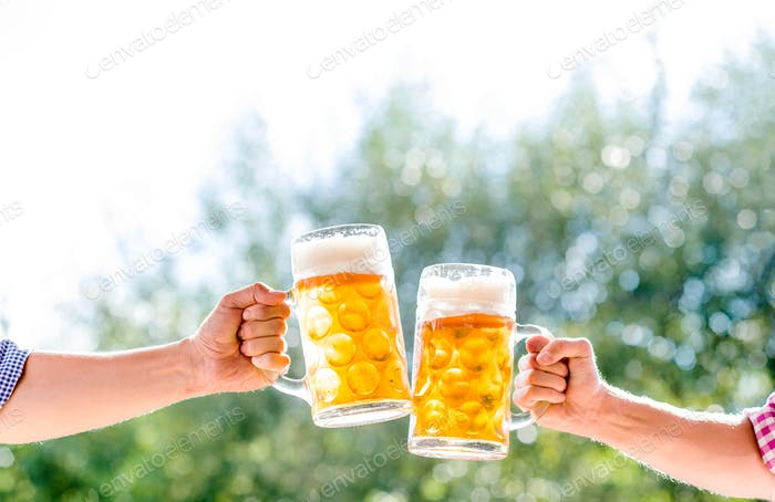 Hands of two men holding mugs of of beer