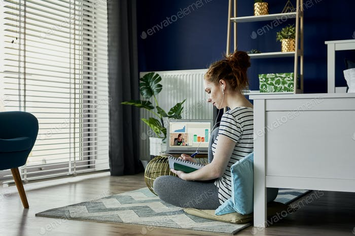Woman sitting on floor and having a video conference