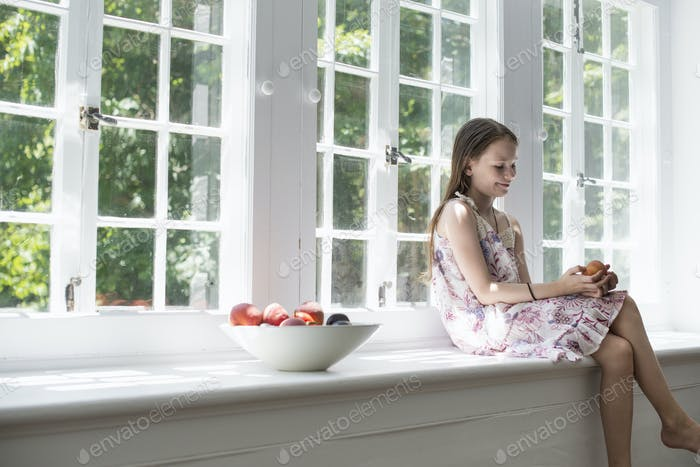 Girl sitting by a window.