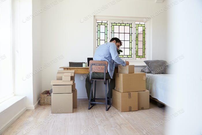 Man In Bedroom Running Business From Home Labeling Goods