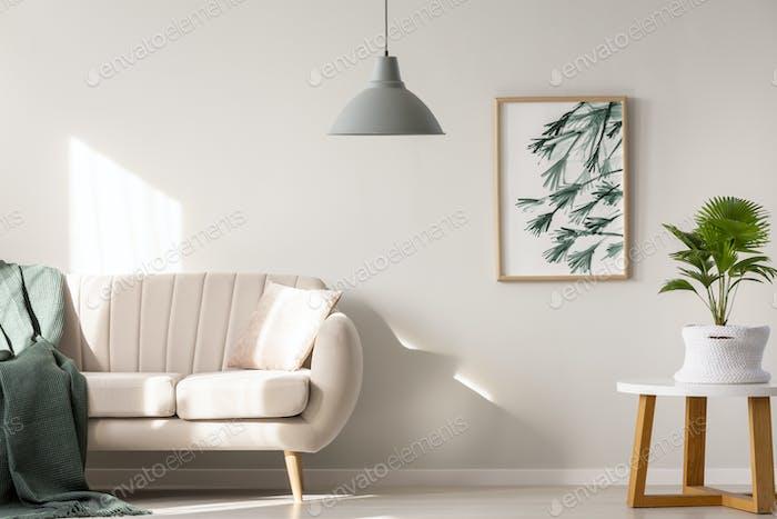 Echtes Foto von einer Couch mit Decke und Kissen neben einem
