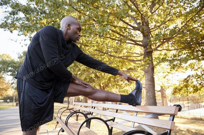 Young black man stretching leg in a Brooklyn park