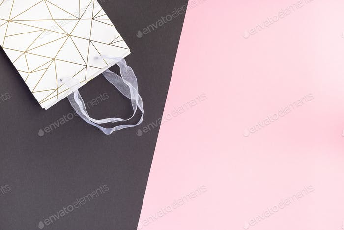 Paper shopping bag on pink and black paper, horizontal, copy space