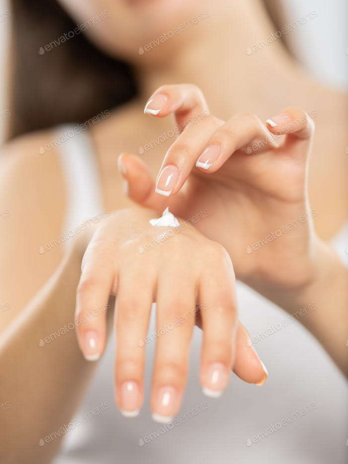 Woman applies a cosmetic moisturizer on her hands.
