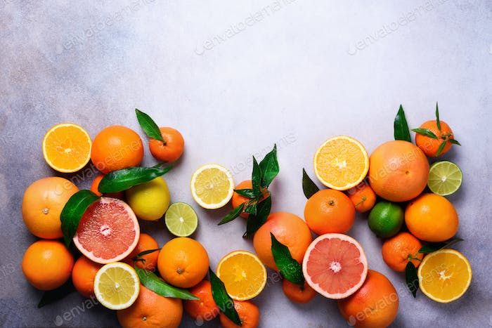 Citrus fruits background. Assorted fresh citrus fruits with leaves. Orange, grapefruit, lemon, lime