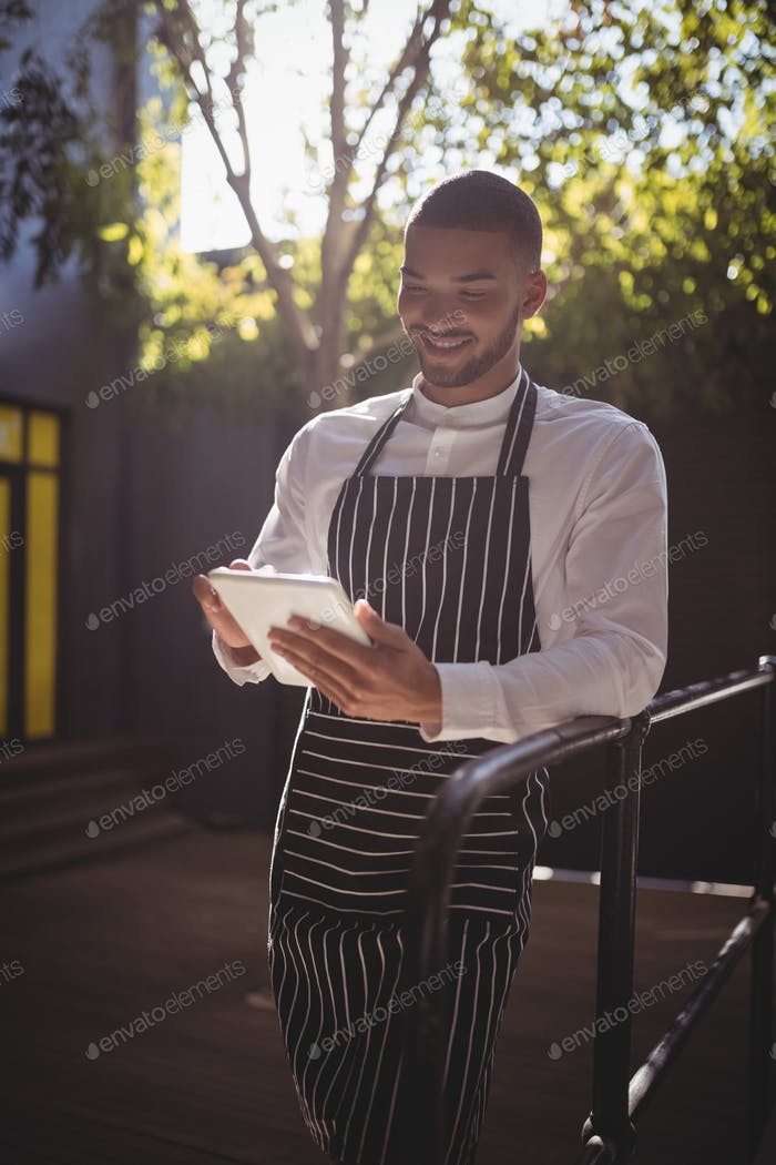 Smiling young waiter using digital tablet while leaning on railing