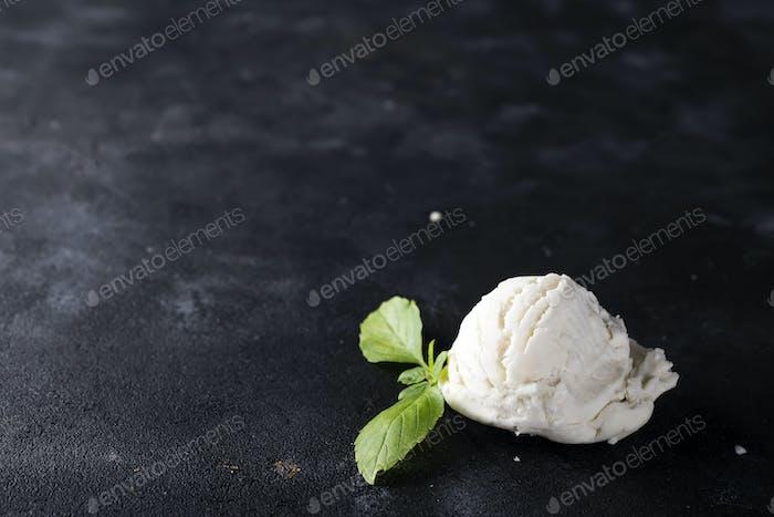 vanilla ice cream ball with green leaves on dark