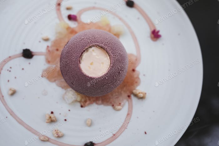 High angle close up of plate of dessert with with a cassis bombe and elderflower yoghurt, choya