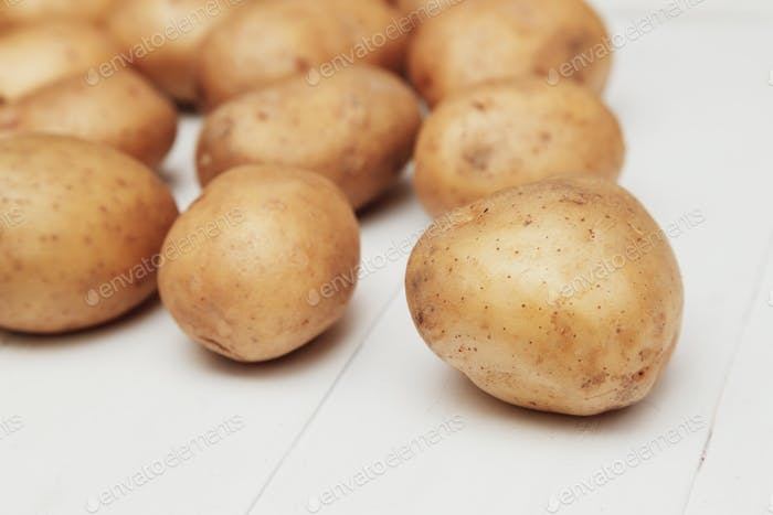 Close up of new potatoes on the white wooden table