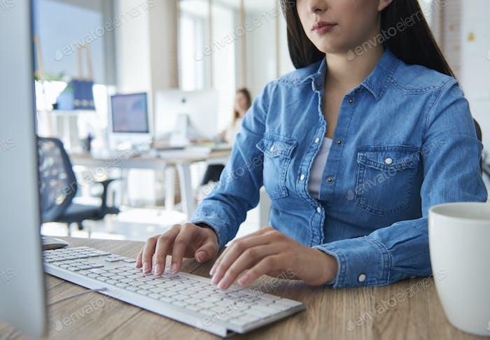 Nahaufnahme der Frau, die auf der Computertastatur tippt