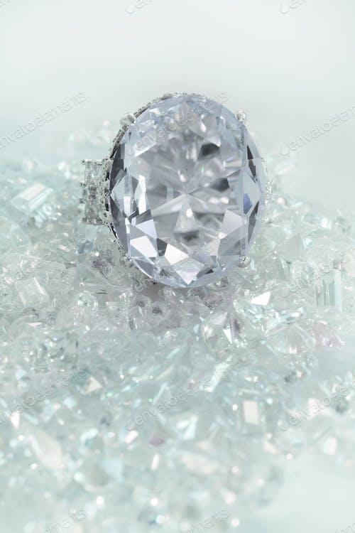 Beautiful large diamond engagement wedding ring sitting on diamonds scattered background