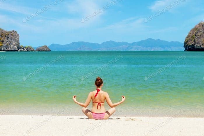 Young woman practice yoga on a beach