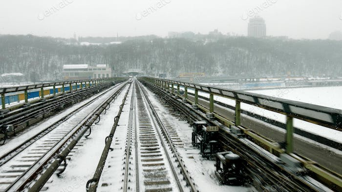 Train moves through the bridge at snow stormy day time.