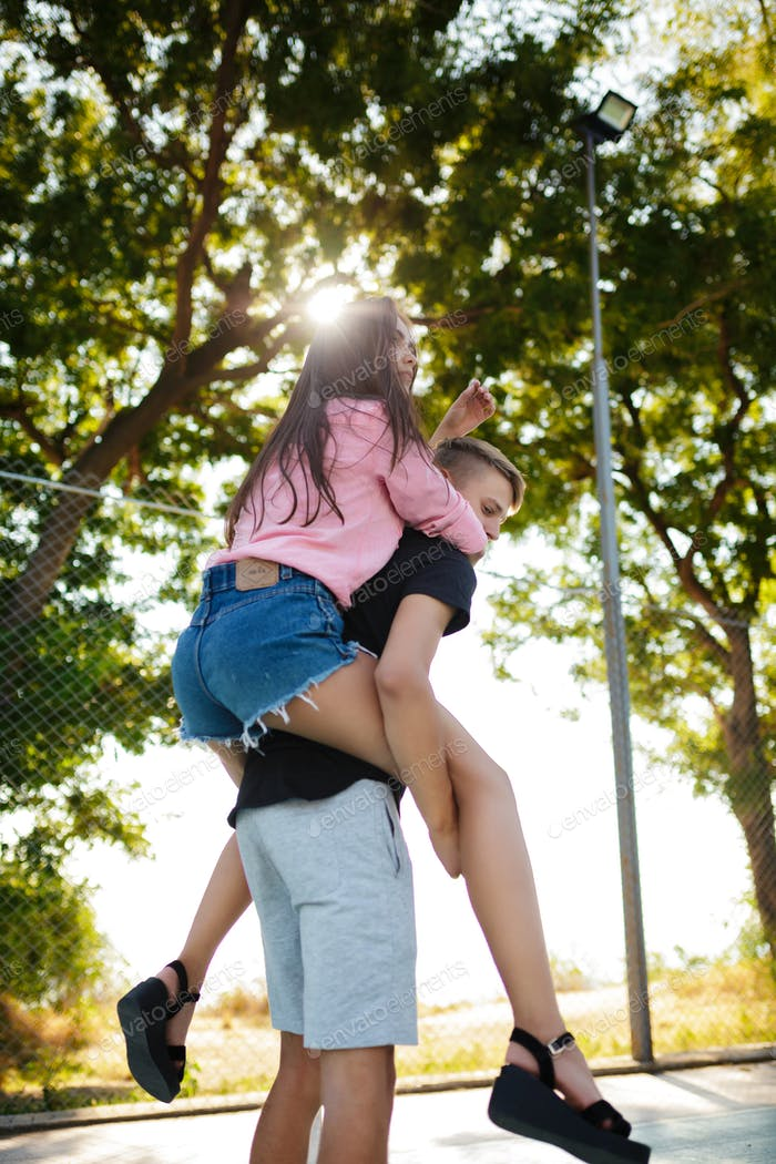 Young boy holding beautiful girl on his back and having fun in park together