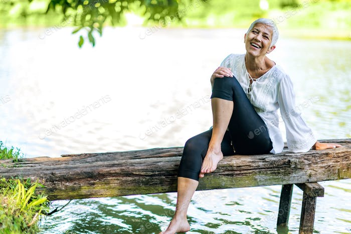 Beautiful mature woman enjoying peace and tranquility of the nature