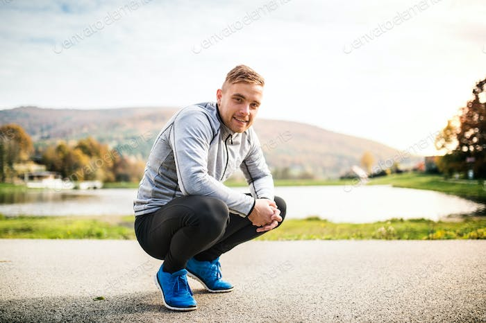 Handsome young runner squatting down.