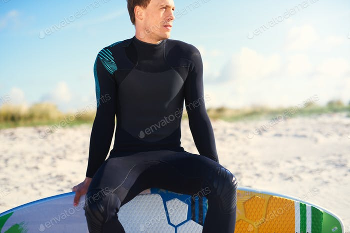 Surfer sitting balanced on the edge of his board