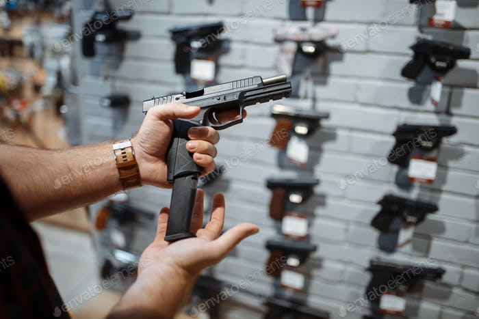 Man choosing new handgun in gun shop