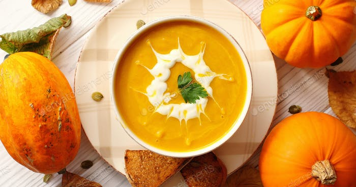 Creamy pumpkin soup in bowl with herb