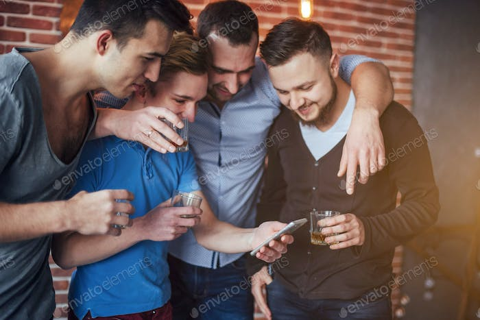 Cheerful old friends communicate with each other and phone watch,  glasses of whiskey in pub