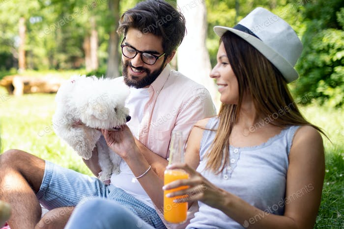 Lifestyle, happy couple resting at a picnic in the park with a dog