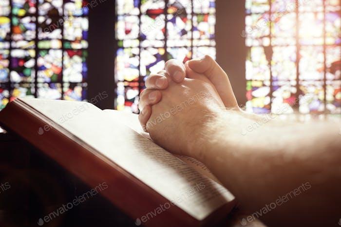 Hände beten auf eine Heilige Bibel