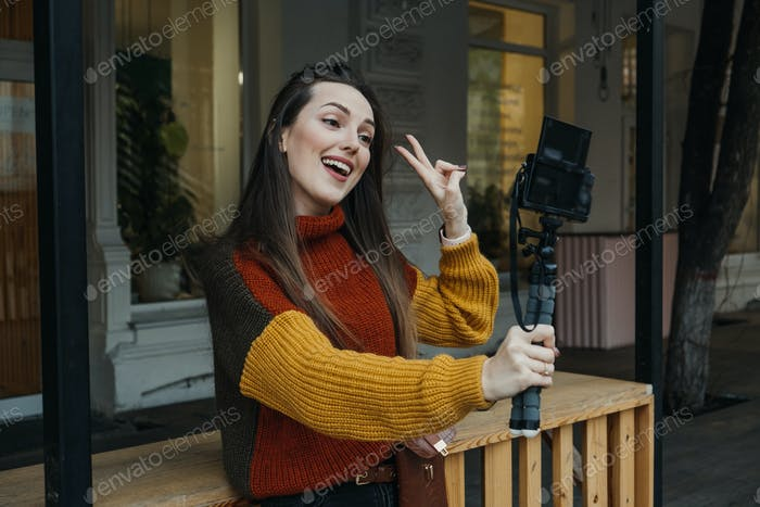 Content creator, blogger, vlogger young woman taking selfies, filming herself and having fun on city