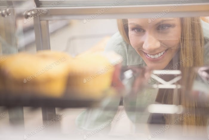 Portrait of a woman looking at new plates with pastries in a supermarket